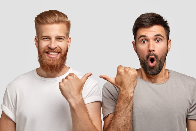Zszokowany nieogolony mężczyzna z ciemnym zarostem wskazuje na swojego towarzysza, nosi szarą koszulkę. wesoły rudy facet z modną fryzurą i końcówkami włosia na faceta. dwóch przyjaciół model kryty na białej ścianie