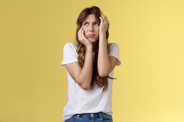 Zszokowany nieśmiały niepewny młoda panikująca kobieta chce płakać stojąc zaniepokojony przestraszony chwycić głowę obiema rękami przestraszony odwrócić wzrok modląc się o pomoc przerażony stać żółte tło przerażony