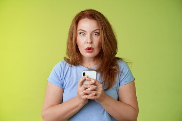 Zszokowany oniemiały pod wrażeniem ruda europejska kobieta w średnim wieku fałd usta zdumiony wow spojrzenie aparat zafascynowany zareagować zdumiony zdumiony odebrana wiadomość trzymaj smartfon intensywna zielona ściana