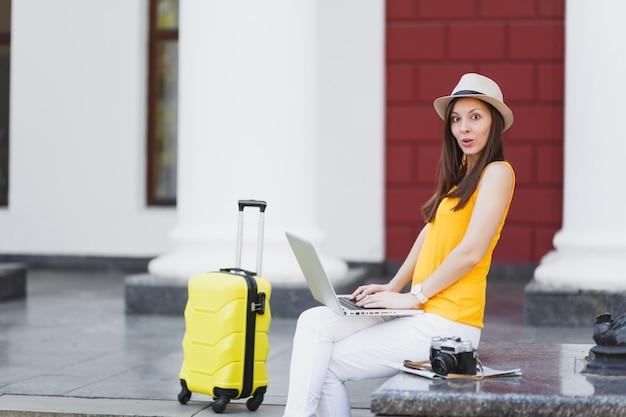 Zszokowany podróżnik turysta kobieta w ubraniach casual, kapelusz z walizką siedzi za pomocą pracy na komputerze typu laptop w mieście na świeżym powietrzu. dziewczyna wyjeżdża za granicę na weekendowy wypad. styl życia podróży turystycznej.