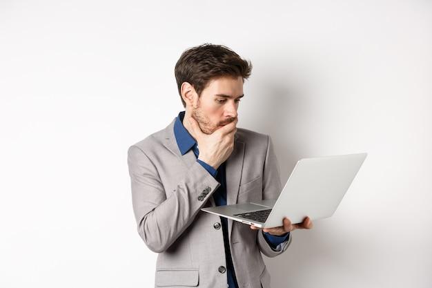 Zszokowany pracownik biurowy w garniturze patrzy zmartwiony na ekranie laptopa, ma problemy w pracy