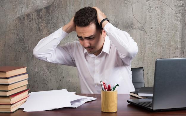 Zszokowany pracownik siedzący przy biurku z kartkami. wysokiej jakości zdjęcie