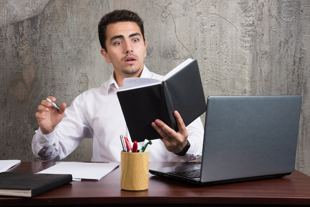 Zszokowany pracownik zaglądający do notesu i siedzący przy biurku. wysokiej jakości zdjęcie
