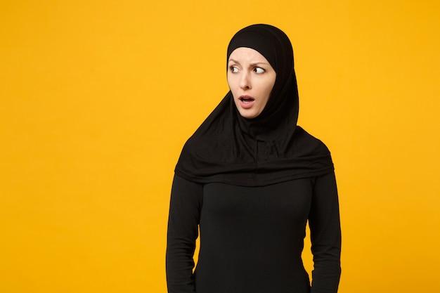 Zszokowany przestraszony całkiem młoda arabska muzułmańska kobieta w czarnych ubraniach hidżab patrząc na bok na białym tle na żółto pomarańczowej ścianie, portret. koncepcja życia religijnego ludzi. makieta miejsca na kopię