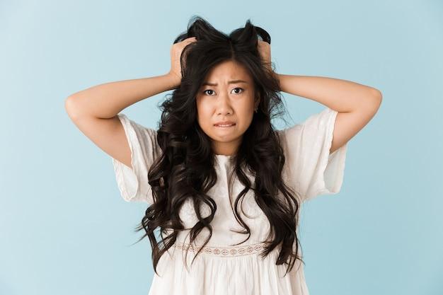 Zszokowany, przestraszony, młoda azjatycka piękna kobieta pozowanie na białym tle nad niebieską ścianą