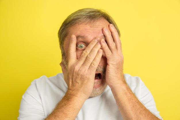Zszokowany, przestraszony, zakrywający twarz rękami. portret kaukaski mężczyzna na białym tle na żółtym tle studio. piękny model męski w białej koszuli.