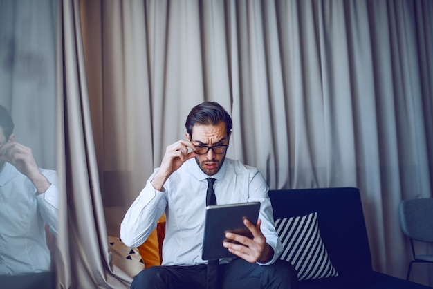 Zszokowany przystojny biznesmen kaukaski brodaty garnitur i krawat siedzi na kanapie w biurze i za pomocą tabletu do pracy.