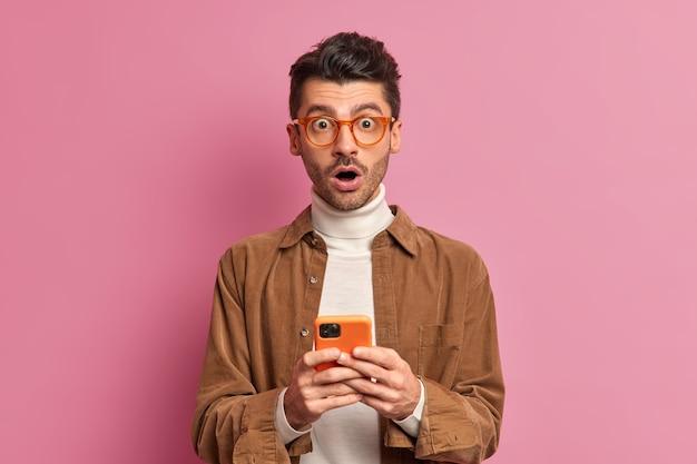 Zszokowany, przystojny, dorosły mężczyzna o europejskim wyglądzie patrzy zdziwiony, trzyma usta w otwartej dłoni i trzyma współczesne telefony komórkowe czyta szokujące wiadomości