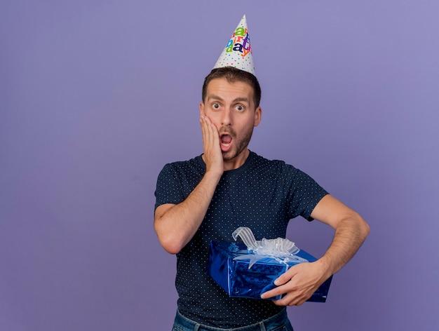 Zszokowany przystojny kaukaski mężczyzna w czapce urodzinowej kładzie rękę na twarzy i trzyma pudełko na białym tle na fioletowym tle z miejsca na kopię