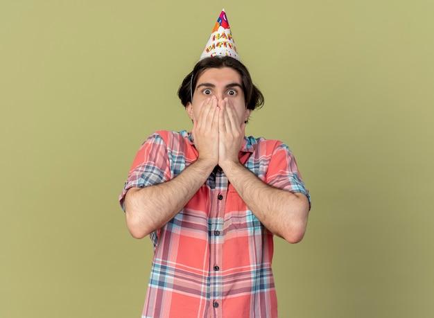 Zszokowany przystojny kaukaski mężczyzna w urodzinowej czapce kładzie ręce na ustach