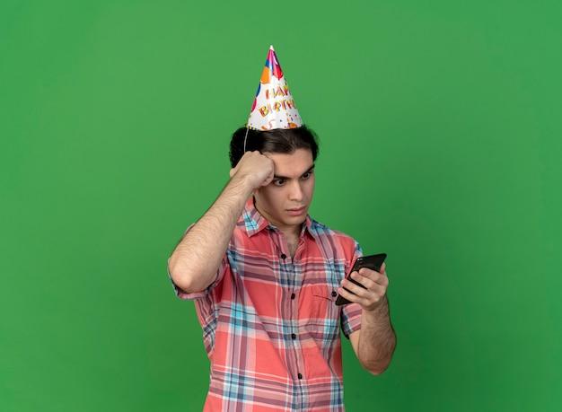 Zszokowany przystojny kaukaski mężczyzna w urodzinowej czapce kładzie rękę na czole, trzymając i patrząc na telefon