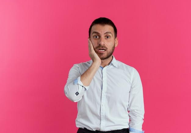 Zszokowany przystojny mężczyzna kładzie dłoń na twarzy patrząc na białym tle na różowej ścianie