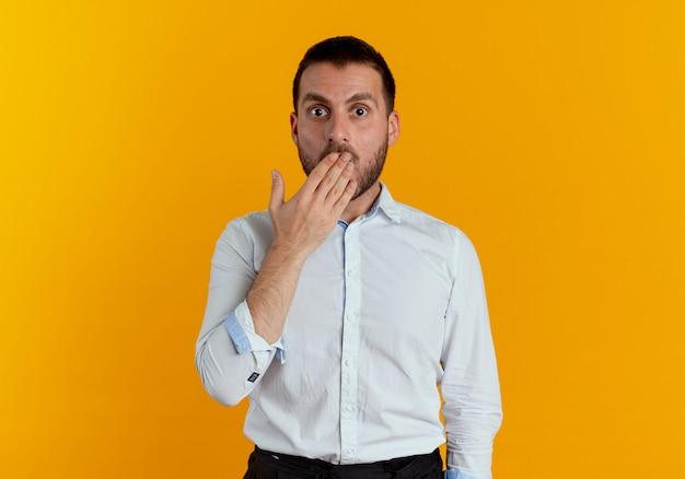 Zszokowany przystojny mężczyzna kładzie dłoń na ustach na białym tle na pomarańczowej ścianie