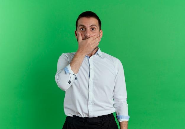 Zszokowany przystojny mężczyzna kładzie dłoń na ustach na białym tle na zielonej ścianie