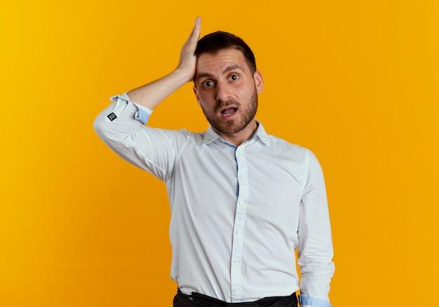 Zszokowany przystojny mężczyzna kładzie rękę na czole na białym tle na pomarańczowej ścianie