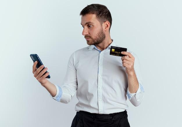 Zszokowany przystojny mężczyzna trzyma kartę kredytową, patrząc na telefon na białym tle na białej ścianie
