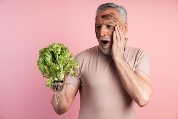 Zszokowany rolnik trzyma w rękach kilka liści sałaty, patrzy na niego