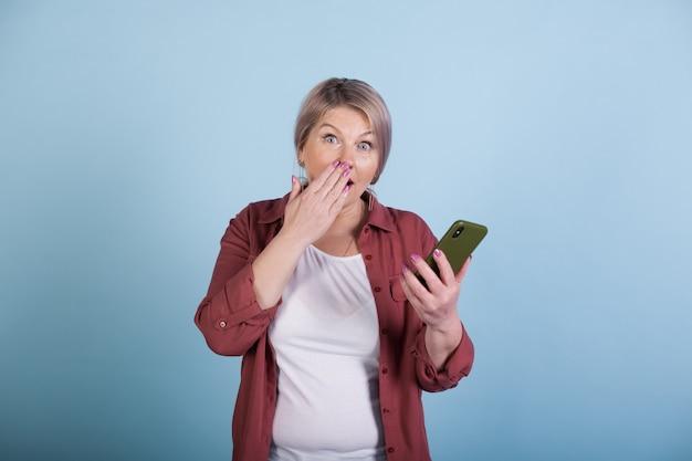 Zszokowany starszy kobieta o blond włosach trzymając telefon patrząc na kamery na ścianie w niebieskim studio
