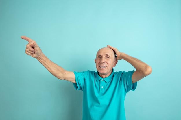 Zszokowany starszy mężczyzna wskazując na bok