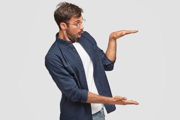 Zszokowany, straszny facet gestykuluje obiema rękami, pokazuje wzrost lub rozmiar rzeczy
