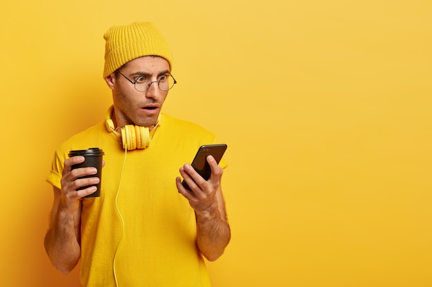 Zszokowany stylowy facet w żółtym stroju i okularach, używa smartfona