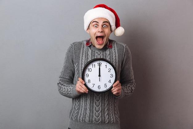 Zszokowany szczęśliwy mężczyzna w swetrze i świątecznym kapeluszu trzyma zegar i patrzy