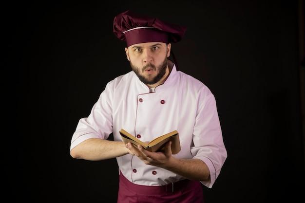 Zszokowany szef kuchni mężczyzna w mundurze trzyma książkę kucharską