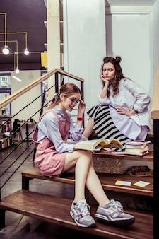 Zszokowany treścią. zajęte, przystojne dziewczyny spędzają czas na drewnianych schodach w coworkingu i czytają materiały