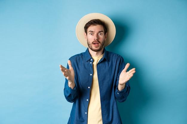 Zszokowany turysta mężczyzna na wakacjach, podnosząc ręce do góry i patrząc na kamerę zaskoczony, reaguje na doniesienia z niedowierzaniem, stojąc na niebieskim tle w słomkowym kapeluszu letnim i koszuli.
