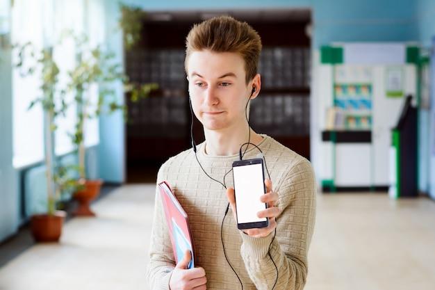 Zszokowany uczeń pokazuje ekran telefonu komórkowego, wygląda na oszołomionego, zaskoczonego