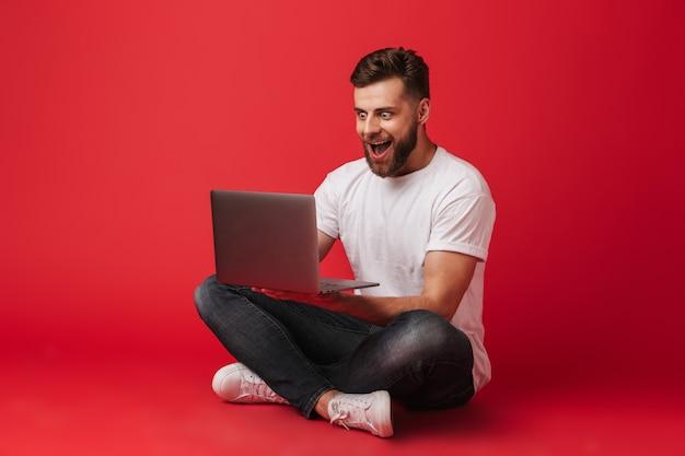 Zszokowany uśmiechnięty młody człowiek siedzi na białym tle przy użyciu komputera przenośnego. patrząc na bok.