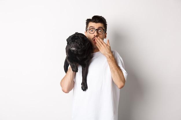 Zszokowany właściciel psa patrzący w kamerę, trzymający szczeniaka na ramieniu i dyszący zdumiony. przystojny młody mężczyzna nosić mops i reagując na reklamę promocyjną, białe tło.