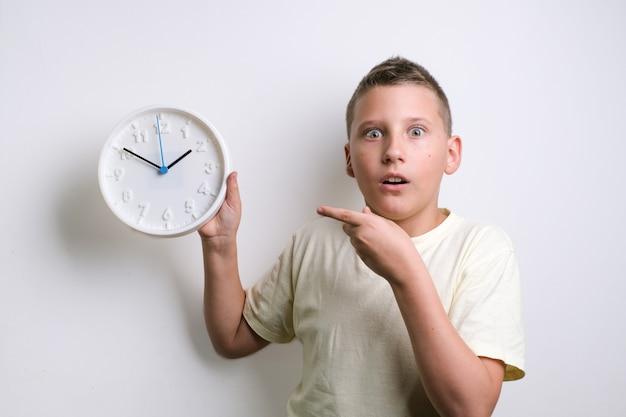 Zszokowany zabawny chłopiec trzymający biały zegar na miejsce na kopię alarmu dziecko na białym tle nad białym tle koncepcja harmonogramu i terminów