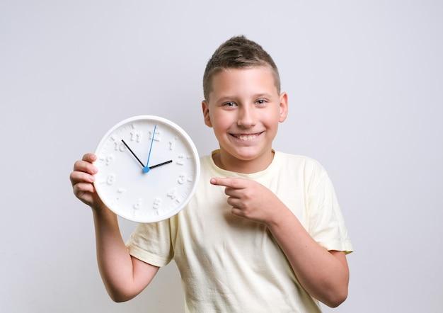 Zszokowany zabawny chłopiec trzymający biały zegar z kopią miejsca na budzik dziecko na białym tle nad białym tłem