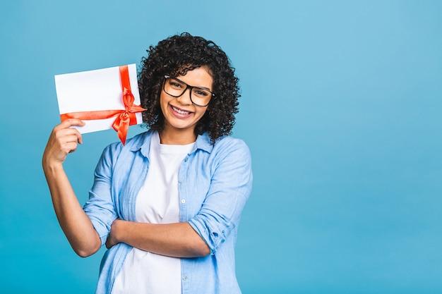 Zszokowany, zaskoczony młody kręcone african american kobieta na białym tle na niebieskim tle portret studio. makieta miejsca na kopię. trzyma bon upominkowy.