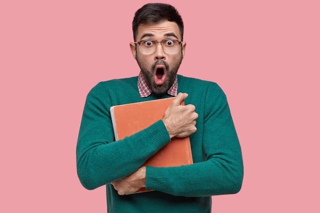 Zszokowany, zaskoczony, nieogolony młody mężczyzna trzyma książkę vintage blisko piersi, wpatruje się w zatkane oczy, ma przerażony wyraz twarzy, nosi okulary optyczne