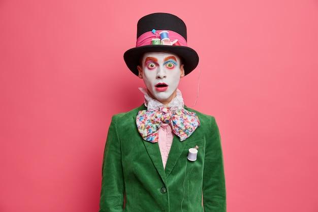 Zszokowany, zawstydzony kapelusznik wpatruje się w kamerę z wyłupiastymi oczami, ubrany w zieloną marynarkę, muszkę i duży kapelusz z kolorowym makijażem, bierze udział w przedstawieniu na różowej ścianie