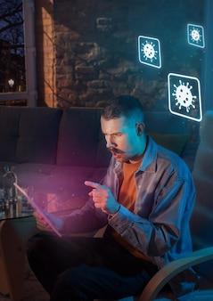 Zszokowany, zdenerwowany i smutny kaukaski mężczyzna używa gadżetów, aby uzyskać informacje o rozprzestrzenianiu się pandemii koronawirusa. pozostać w domu, aby być bezpiecznym. analizowanie sytuacji ze światową liczbą przypadków, opieką zdrowotną, medycyną.