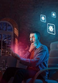 Zszokowany, zdenerwowany i smutny kaukaski mężczyzna używający gadżetów, aby uzyskać informacje o pandemii koronawirusa