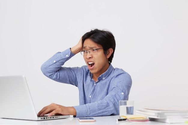 Zszokowany zdezorientowany azjatycki młody biznesmen w okularach z ręką na głowie i otworzył usta pracując z laptopem przy stole nad białą ścianą