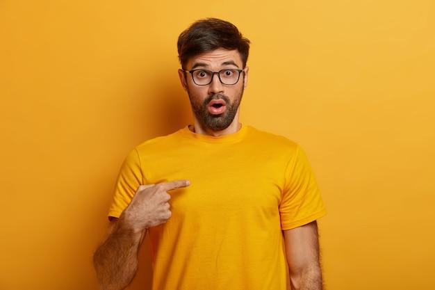 Zszokowany zdezorientowany mężczyzna z gęstą brodą wskazuje na siebie