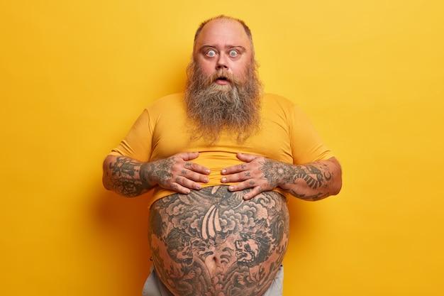 Zszokowany zdumiony hipster mężczyzna trzyma ręce na brzuchu z tatuażem wystającym z koszulki, zaskoczony, że widzi jego wagę, ma długą, gęstą brodę, pozuje na żółtej ścianie. facet pokazuje duży brzuch