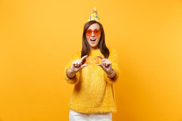 Zszokowany zdumiony młoda kobieta w pomarańczowych okularach serca i urodzinowym kapeluszu trzymając kartę kredytową, ciesząc się wakacjami, świętując na białym tle na żółtym tle. ludzie szczere emocje, koncepcja stylu życia.