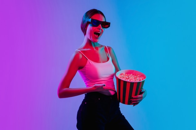 Zszokowany, zdumiony. portret młodej kobiety rasy kaukaskiej na tle gradientu niebiesko-fioletowe studio w świetle neonu. pojęcie młodości, ludzkie emocje, wyraz twarzy, sprzedaż, reklama. piękny model brunetka.