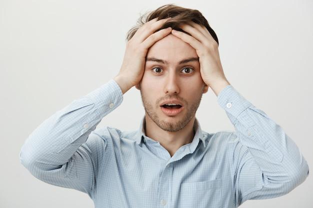 Zszokowany, zmartwiony mężczyzna trzyma ręce na głowie zmartwiony, ma problemy