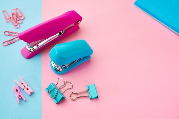 Zszywacz i spinacze do papieru zbliżenie, tło niebieskie i różowe. artykuły biurowe, przybory szkolne