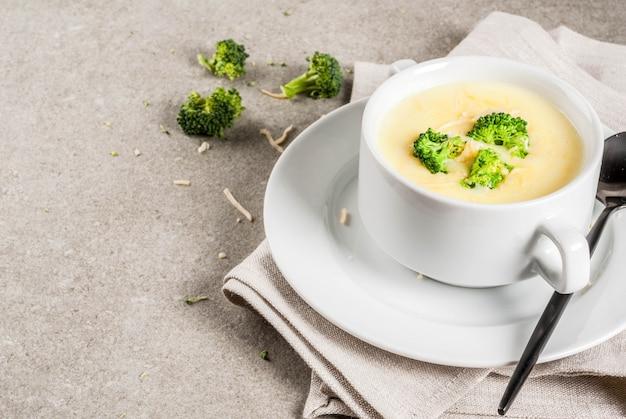 Zupa brokułowa, serowa i z kurczaka, na szarym stole z kamienia, copyspace