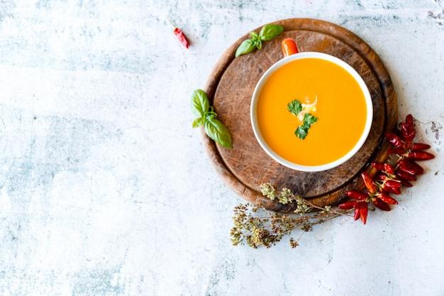Zupa dyniowa i marchewkowa ze śmietaną na szarym kamieniu