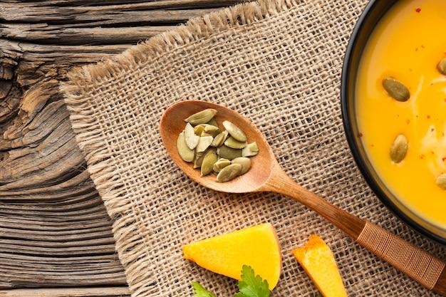 Zupa dyniowa leżąca płasko w misce i drewniana łyżka z ziarnami