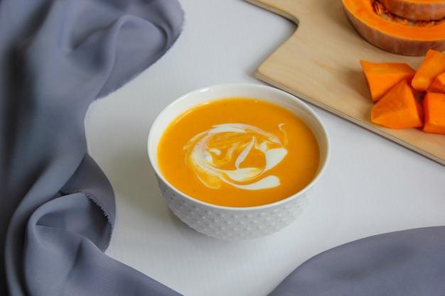 Zupa dyniowa na białym tle z szarym materiałem i plasterkami dyni piżmowej